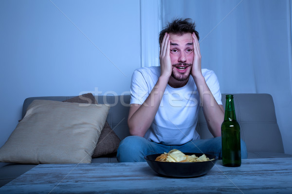 Young man watching TV at nighttime with chips and beer Stock photo © Spectral