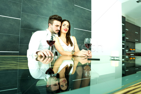 A romantic couple with a glass of wine in the dining room Stock photo © Spectral