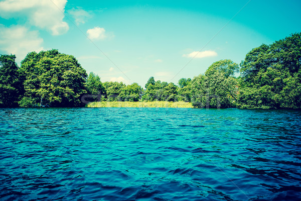 Lake with blue water and green trees Stock photo © Sportactive