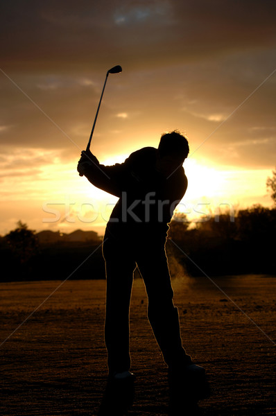 A left handed golfer practices early morning with a beautiful sunrise.  Stock photo © Sportlibrary