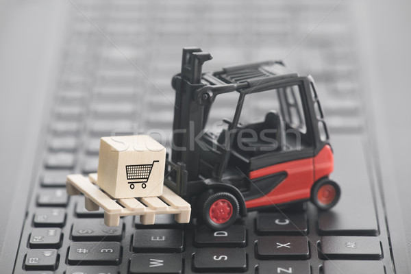 Forklift with shopping cart graphic on wooden block over laptop keyboard  Stock photo © sqback