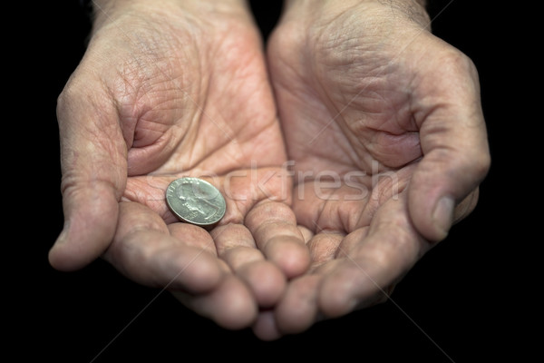 Stock photo: Poverty. Old hands with a single coin of 25 cents