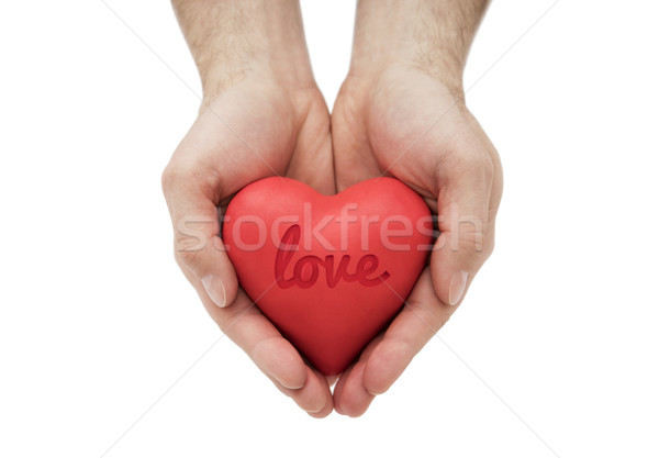 Red heart with imprinted love word in man's hands.  Stock photo © sqback