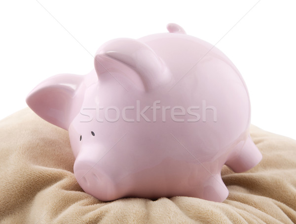 Piggy bank lying down on a pillow. Stock photo © sqback