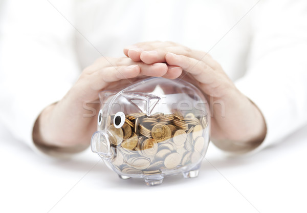 Protect your money. Transparent piggy bank with coins covered by hands.  Stock photo © sqback