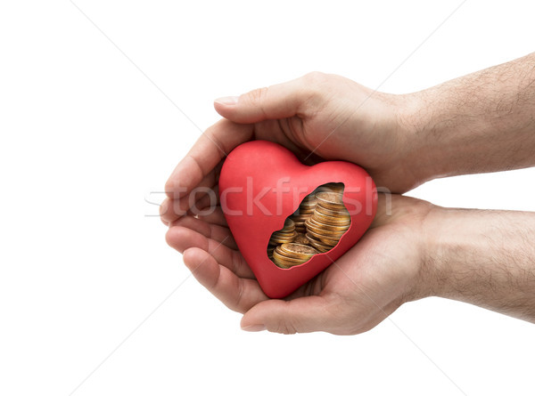 Red heart with golden coins in hands over white background with clipping path  Stock photo © sqback