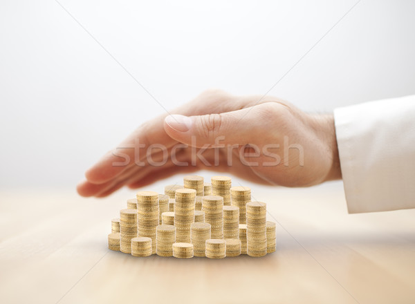 Stack of golden coins covered by hand. Savings protection concept  Stock photo © sqback