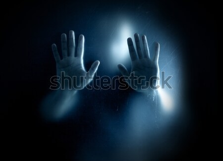 Stock photo: Shadowy figure trapped behind a dusty scratched glass