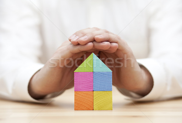 Colorful wooden block house protected by hands  Stock photo © sqback
