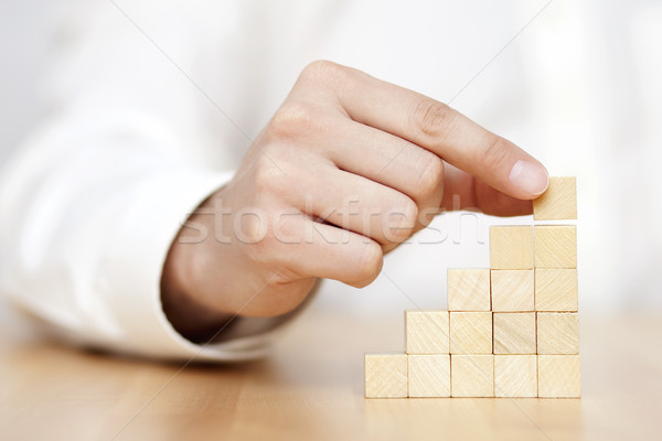 Man's hand put wooden blocks in the shape of a staircase. Business success concept.  Stock photo © sqback