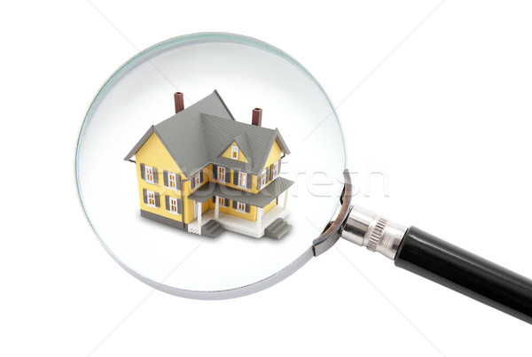 House searching concept with a magnifying glass isolated on white background  Stock photo © sqback
