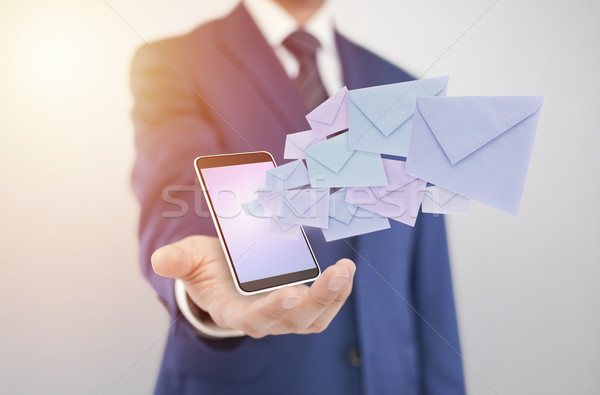 Businessman with smartphone with envelopes coming out of the screen  Stock photo © sqback