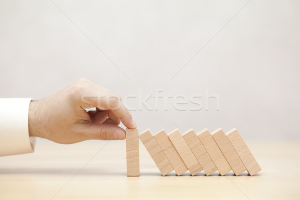 Man's hand stopping the domino effect. Concept image for business strategy and crisis solution.  Stock photo © sqback