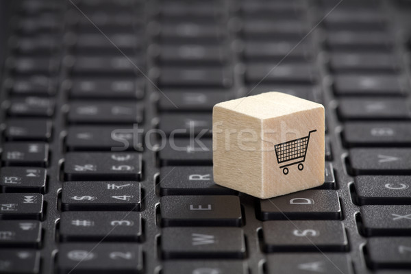 Wooden block with shopping cart graphic on laptop keyboard. Online shopping concept.  Stock photo © sqback