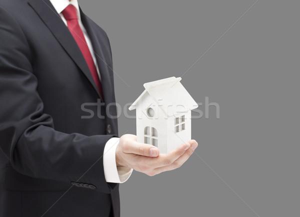 Işadamı beyaz oyuncak ev minyatür el Stok fotoğraf © sqback