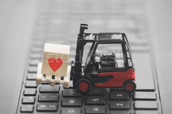 Forklift with red heart symbol on wooden block over laptop keyboard  Stock photo © sqback