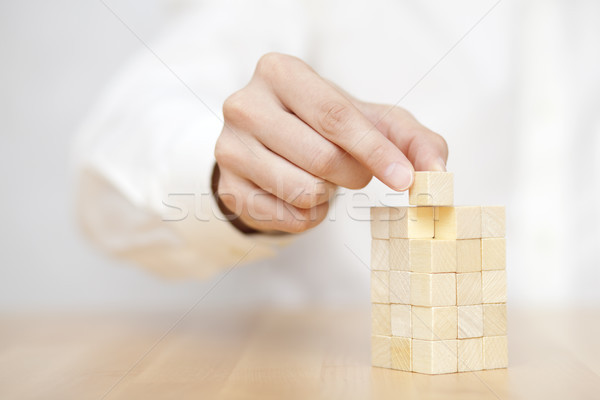 Man's hand adding the last missing wooden block into place. Business success concept.  Stock photo © sqback