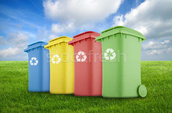 Four colorful recycle bins on green grass.  Stock photo © sqback
