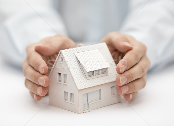 Property insurance. House miniature covered by hands.  Stock photo © sqback