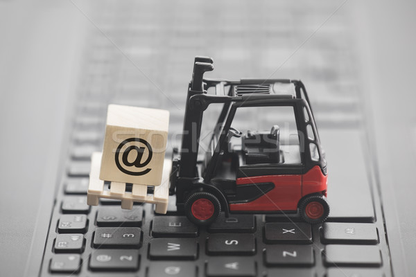 Forklift with email symbol on wooden block over laptop keyboard Stock photo © sqback