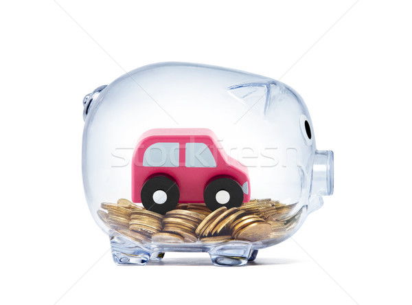 Car toy on coins inside transparent piggy bank with clipping path  Stock photo © sqback