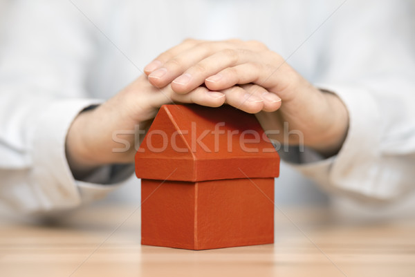 Small orange house protected by hands  Stock photo © sqback