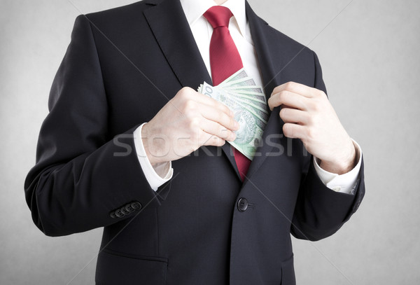 Corruption. Man putting polish money in suit jacket pocket.  Stock photo © sqback