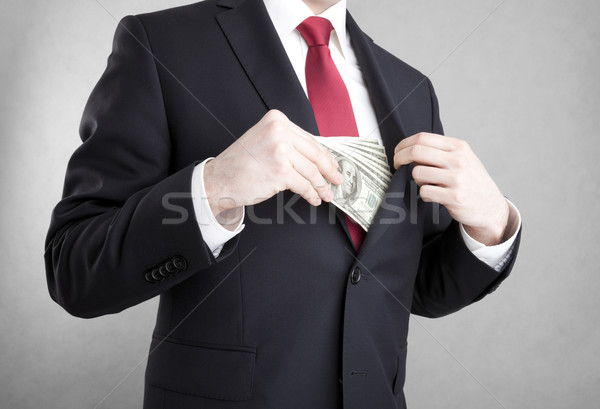 Corruption in business. Man putting money in suit jacket pocket.  Stock photo © sqback