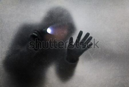 Thief with flashlight behind a dusty scratched glass  Stock photo © sqback