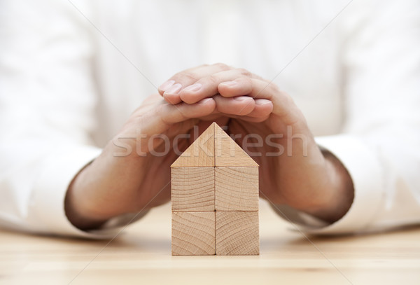Wooden block house protected by hands  Stock photo © sqback