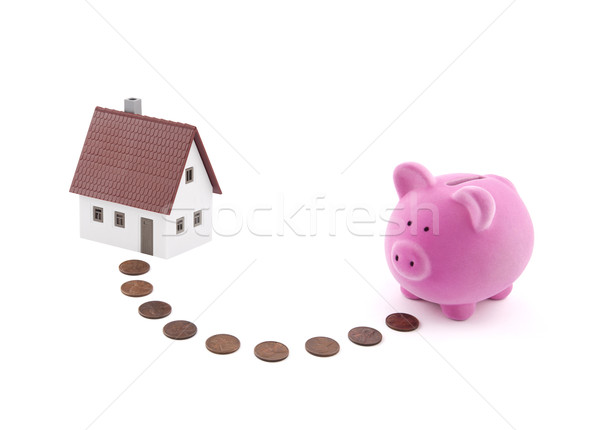 Saving for a house. Piggy bank with coins and house miniature. Stock photo © sqback
