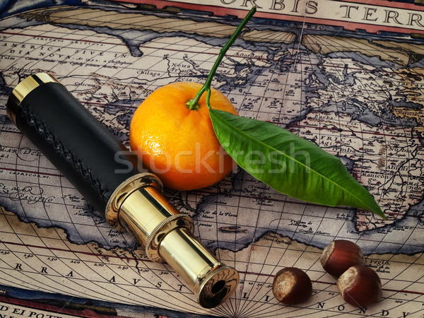 vintage telescope and mandarine at antique map Stock photo © SRNR