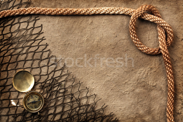 Rough paper with compass, rope, and netting Stock photo © SSilver
