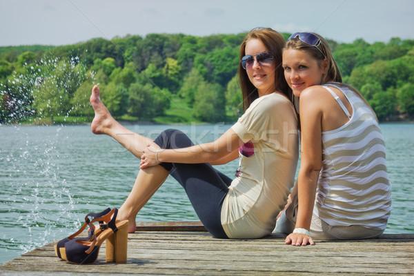 Mutlu tatil iki genç kadın oturma iskele Stok fotoğraf © Steevy84