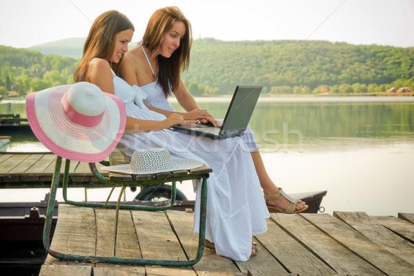 Tatil Internet iki genç kadın oturma iskele Stok fotoğraf © Steevy84