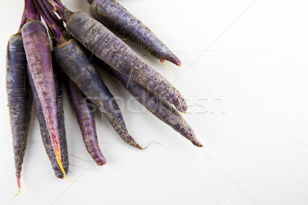 Bunch of heirloom purple carrots, over white and wooden backgrou Stock photo © stefanoventuri