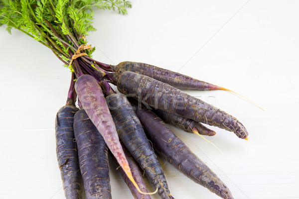 Stock photo: Bunch of heirloom purple carrots, over white and wooden backgrou