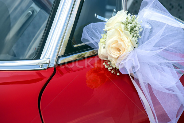 Little flower bouquet with white bow over a red car Stock photo © stefanoventuri