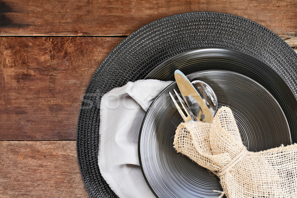 Place Setting of Black Dinnerware over Wooden Background Stock photo © StephanieFrey