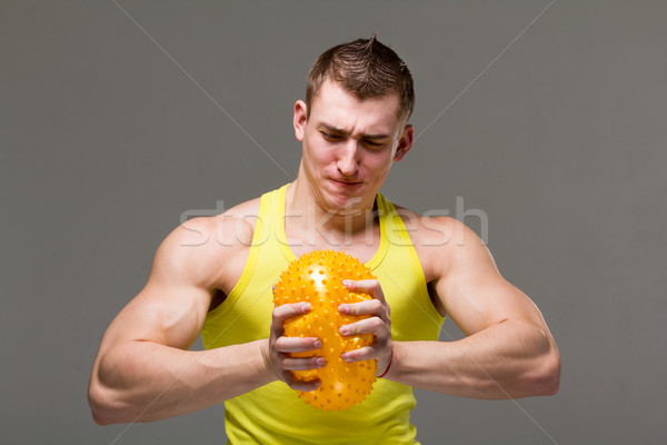 Muscular young man flexing arm muscles Stock photo © stepstock
