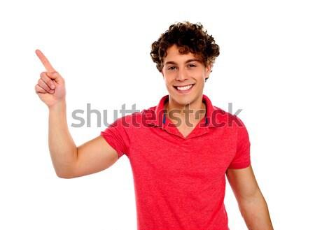 Casual guy indicating upwards Stock photo © stockyimages