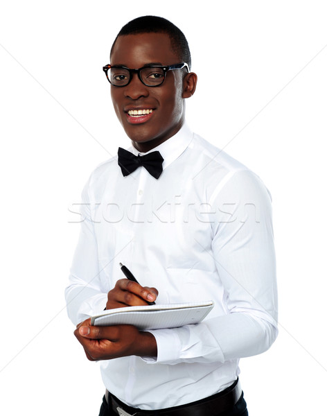 Smart african writing on clipboard Stock photo © stockyimages
