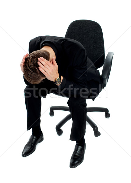 Frustrated young man sitting on chair Stock photo © stockyimages