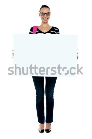 College girl holding white ad board, full length shot Stock photo © stockyimages