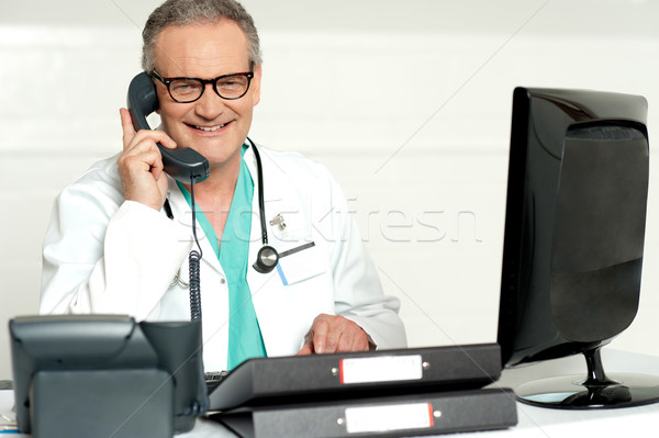 Aged doctor attending call in front of lcd screen Stock photo © stockyimages