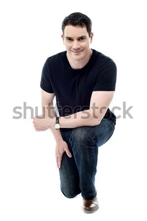 Young man sitting in squatting position Stock photo © stockyimages