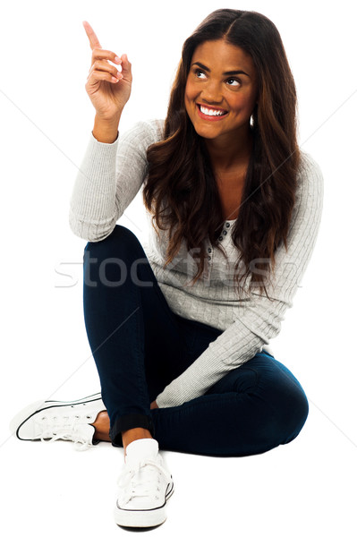 Young woman looking and pointing upwards Stock photo © stockyimages