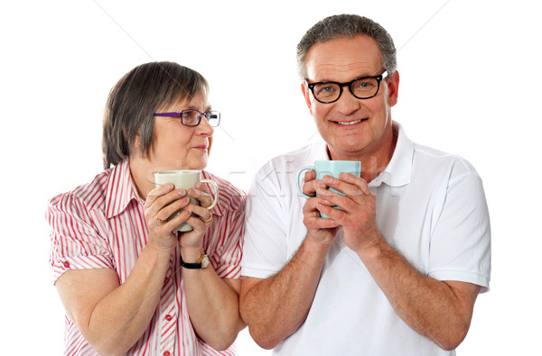 Romantic senior couple holding coffee mugs Stock photo © stockyimages