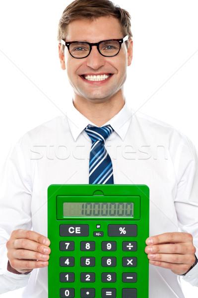 Vállalati férfi mutat nagy zöld számológép Stock fotó © stockyimages