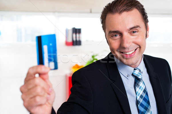 Handsome male executive holding cash card Stock photo © stockyimages